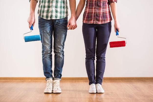 Молодая пара с валиком, делая ремонт дома.