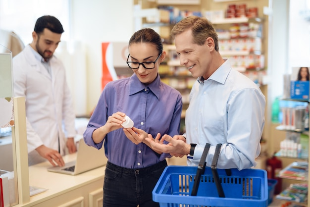 男と女の薬局で薬を選ぶ。
