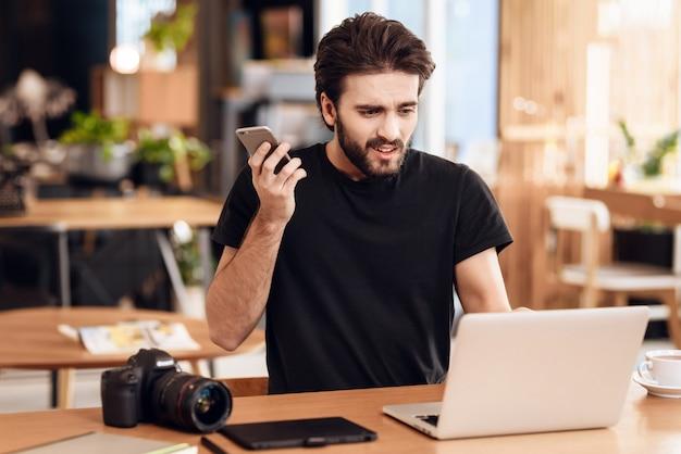 フリーランサーは机に座ってラップトップで電話でひげを生やした男。