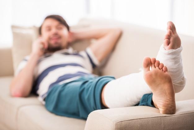 男は足を骨折したソファーに横になっていると電話で話しています。