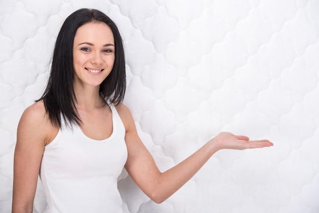 整形外科のマットレスを持つ若い女性の笑みを浮かべてください。