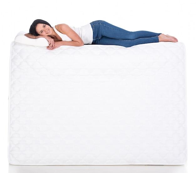 Молодая женщина лежит на матрасе.