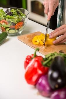 男の手は台所で野菜サラダを調理します。