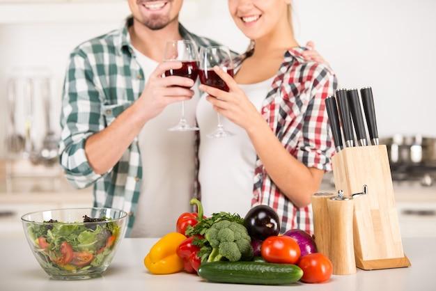 Молодая красивая пара пьют вино на кухне.