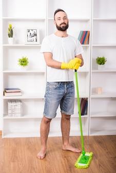 男は家で掃除をしています。