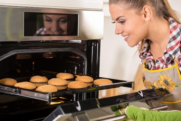若くてきれいな女性がオーブンからクッキーを引っ張る。