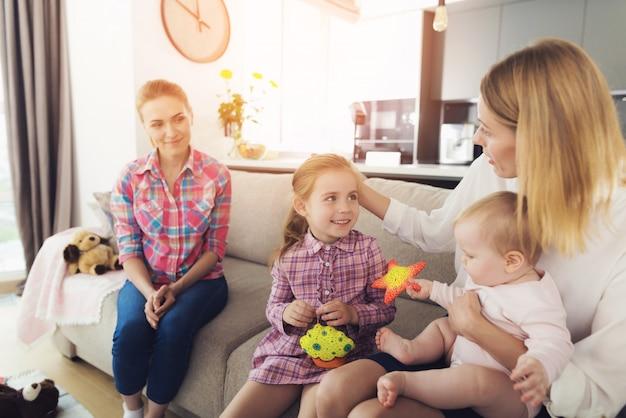 Мама с милыми детьми сидит на диване возле няни