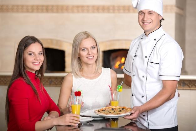 ウェイターは、レストランで若い女性にピザを提供しています。