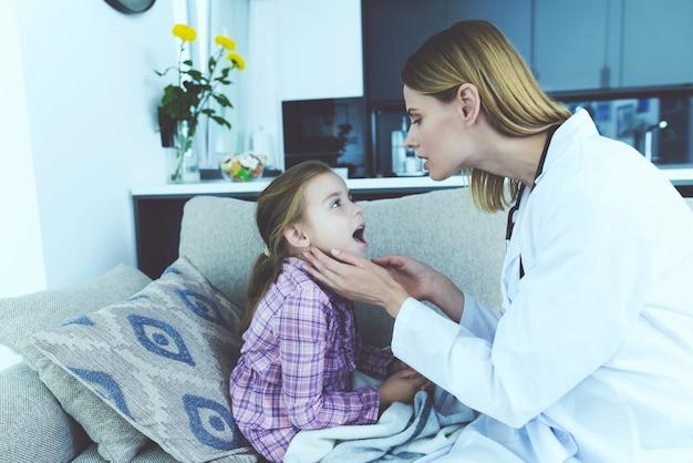 Женщина-врач осматривает довольно больного ребенка дома