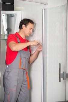 プロの配管工がシャワーを修理しています。