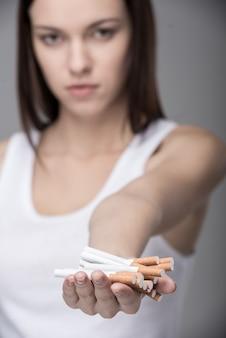 多くのタバコを持つ若い女