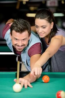 若いカップルは暗いビリヤードクラブでビリヤードを果たしています。