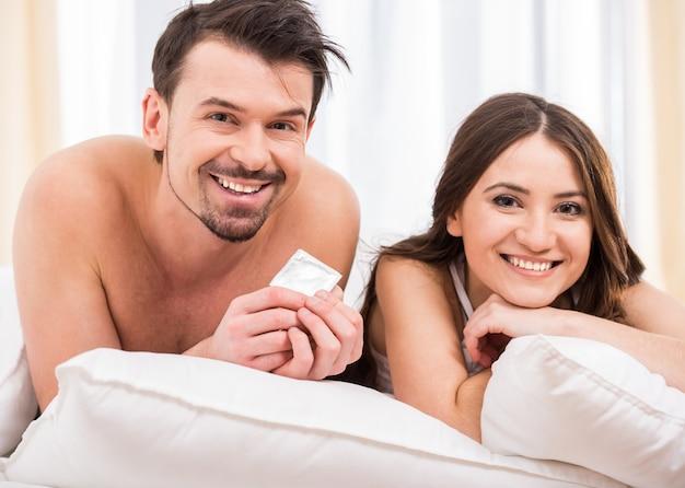 Молодая привлекательная пара в постели с презервативом.