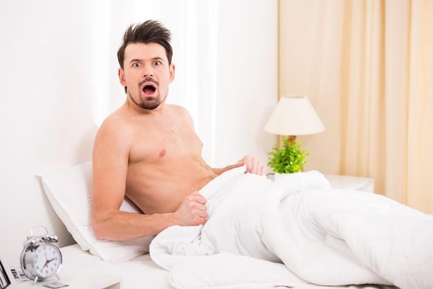 ベッドの中で驚いてショックを受けた半分裸の若い男。