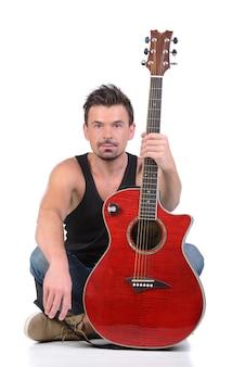 男は大きなギターと一緒に座っています。