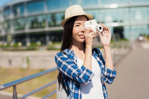かわいい女の子は町で歩き、写真を撮る。