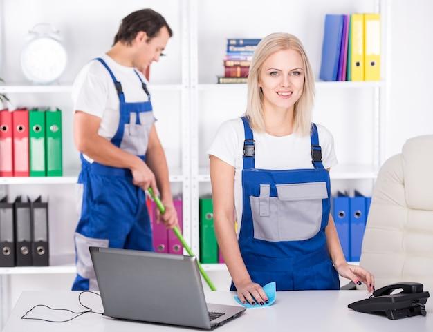 若いカップルのプロの洗剤が事務所を掃除しています。