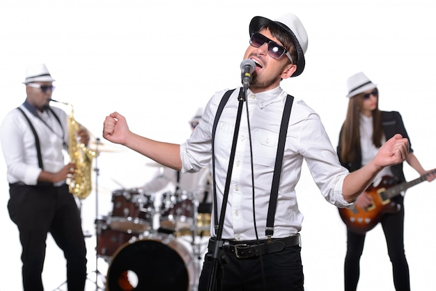 メガネと帽子をかぶった男がマイクに向かって歌います。
