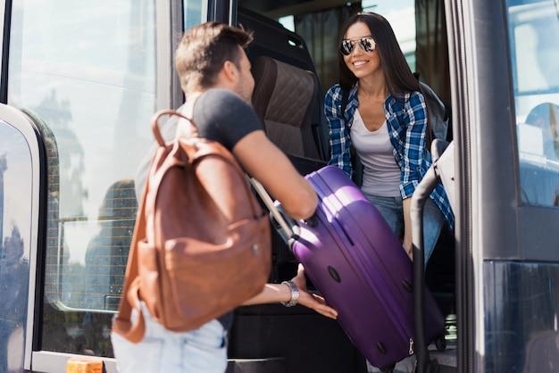 Туристы садятся в автобус. парень помогает девушке с багажом.