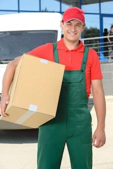 Улыбающийся молодой мужской почтальон курьерской доставки человек.