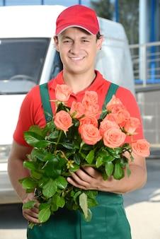 笑顔の若い宅配便は花の配達を開催しています。