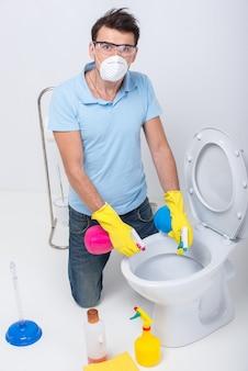 男が洗剤で便器を掃除しています。