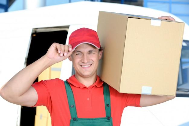 彼の肩に箱を持つ男は男のための配達を運ぶ。