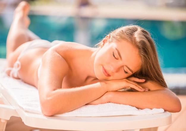 Красивая женщина лежит на шезлонге у бассейна.