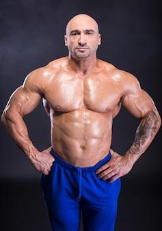 男のボディービルダーは彼の完璧な筋肉組織を示しています