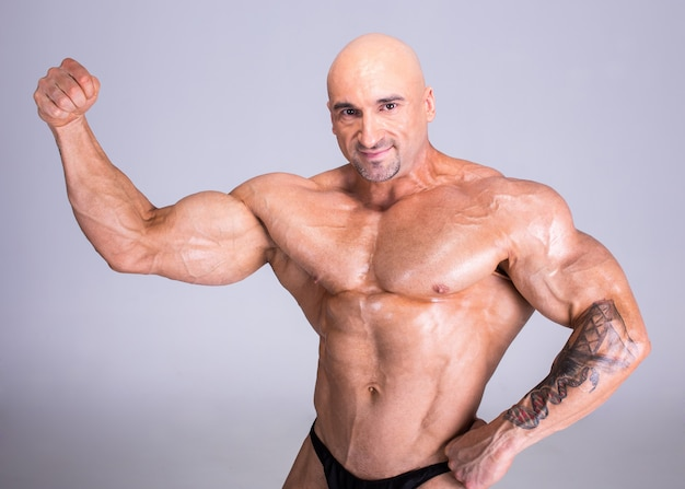 ボディービルダーは彼の完璧な筋肉ボディを実演しています。