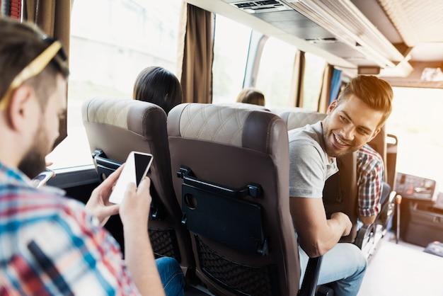 男はバスに乗っています。彼は向きを変えて乗客を見た。