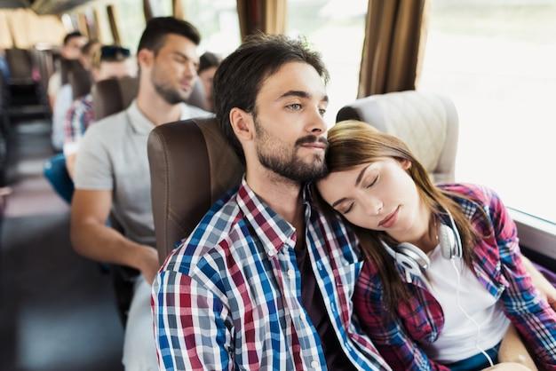 恋人のカップルは現代旅行バスで休憩を持っています。