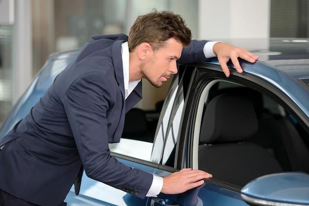 ビジネスマンがディーラーで車を調べます。