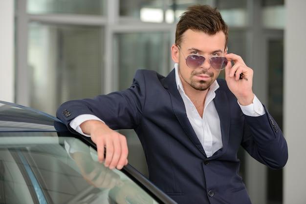 男は車のディーラーに立っている間カメラを見ています。