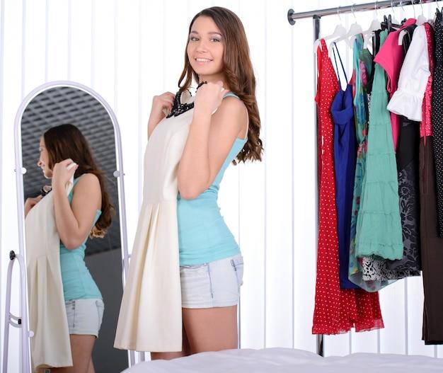 女性はたくさんのドレスと彼女の洋服棚のそばに立つ