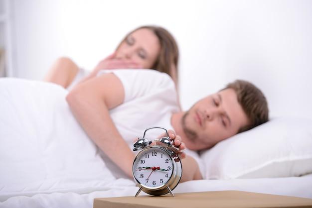 目覚まし時計が付いているベッドで一緒に寝ている若いカップル