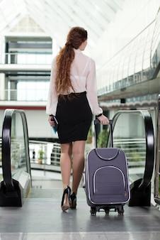 空港でスーツケースを持つ若いビジネス女性。