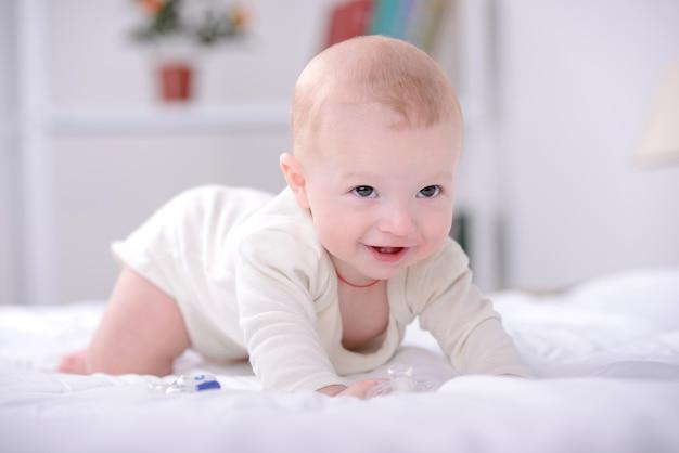 ベッドで遊んでいる小さな赤ちゃんの肖像画。