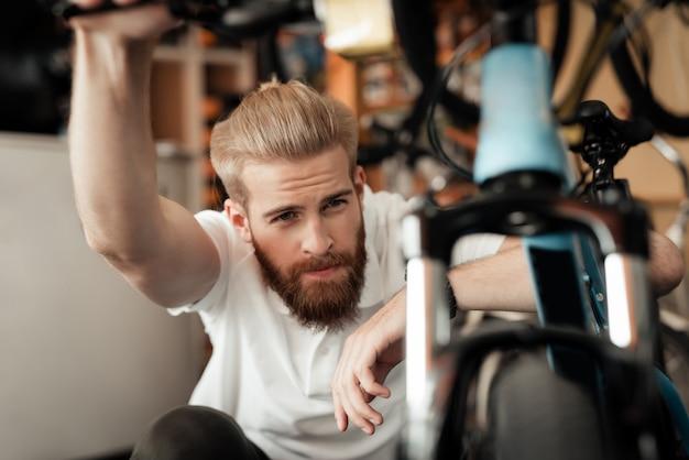 自転車ワークショップでサイクルの詳細を見ている男