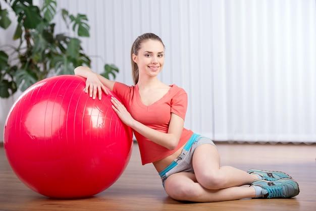 フィットネスボールを持つ若い美しい女性。