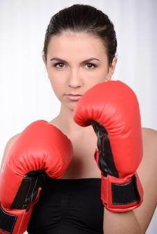ボクシンググローブの女の子がラックに立ちます。