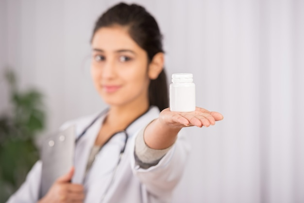 インドの医者が薬で白いコートを着ています。