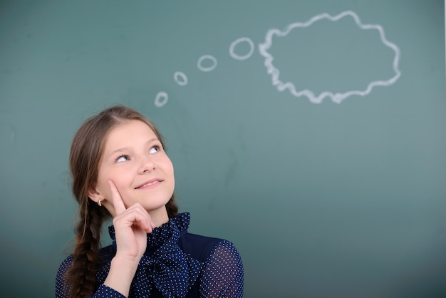 学校の小さな女の子が雲を見ています。