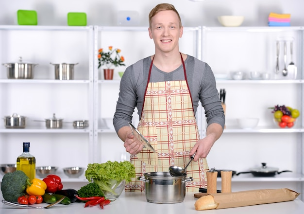 ハンサムな男が自宅の台所でサラダを準備します。