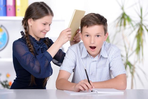 彼は勉強するように少女は頭の上で少年を打つ。