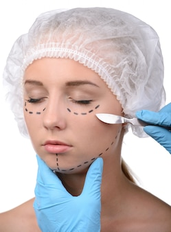 Доктор нарисовал на лице девушки контурное пластиковое лицо.