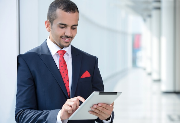 アジア系のビジネスマン、タブレットを使用して、オフィスに立っています。