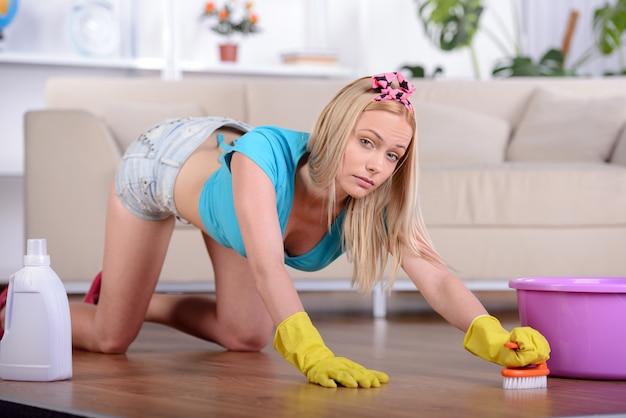 美しい主婦が自宅の床を掃除する