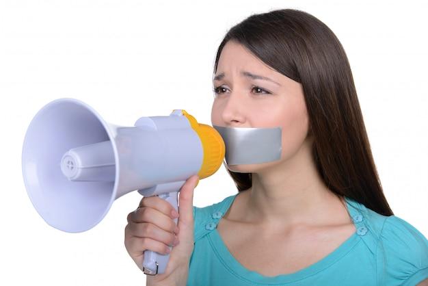 Расстроенная девушка с самоклеющейся лентой над ее ртом.