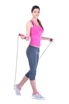 縄跳びの縄を持つ美しいフィットネス若い女性。